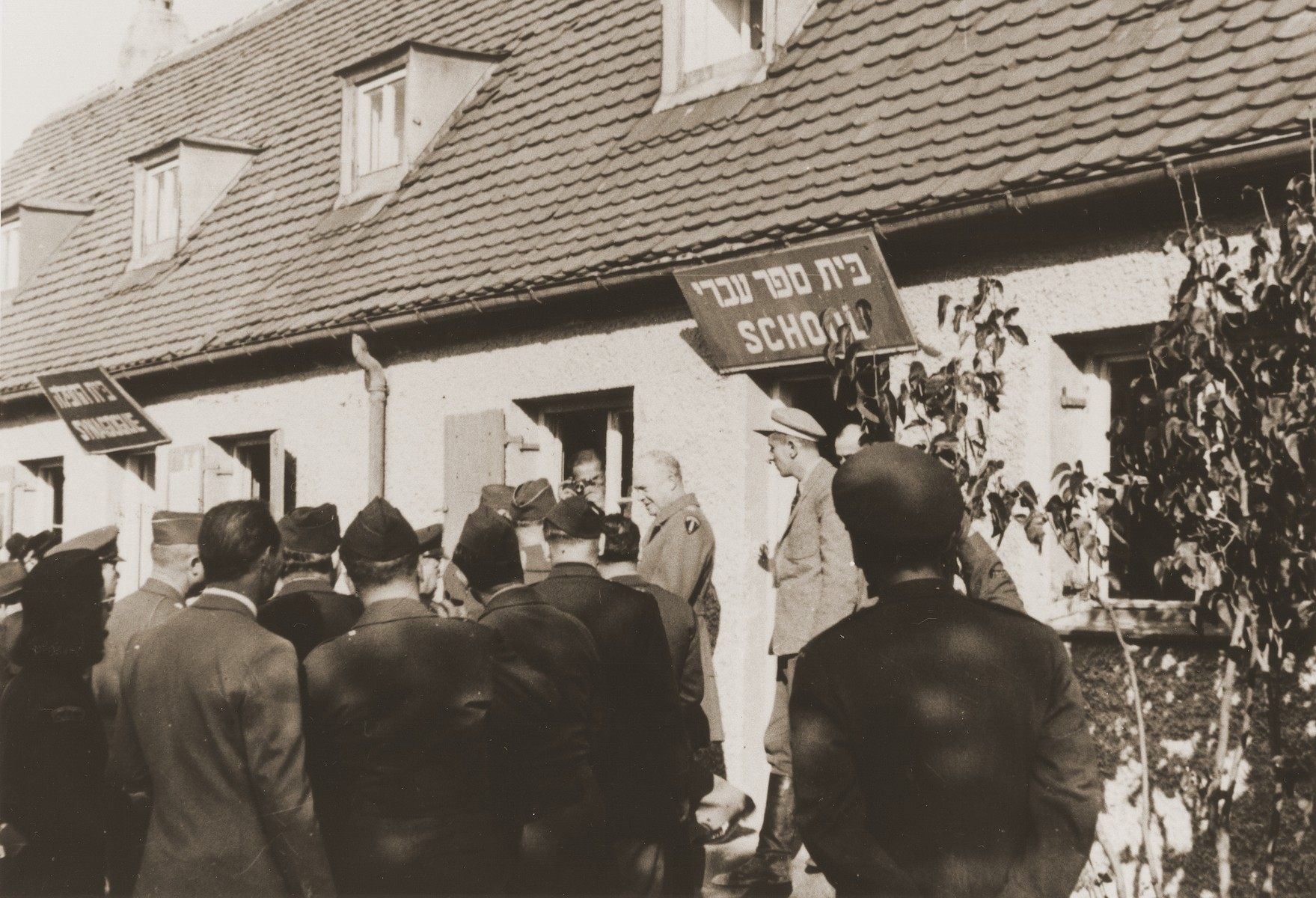 General Dwight Eisenhower visits the school and synagogue during an official tour of the Neu Freimann displaced persons camp.