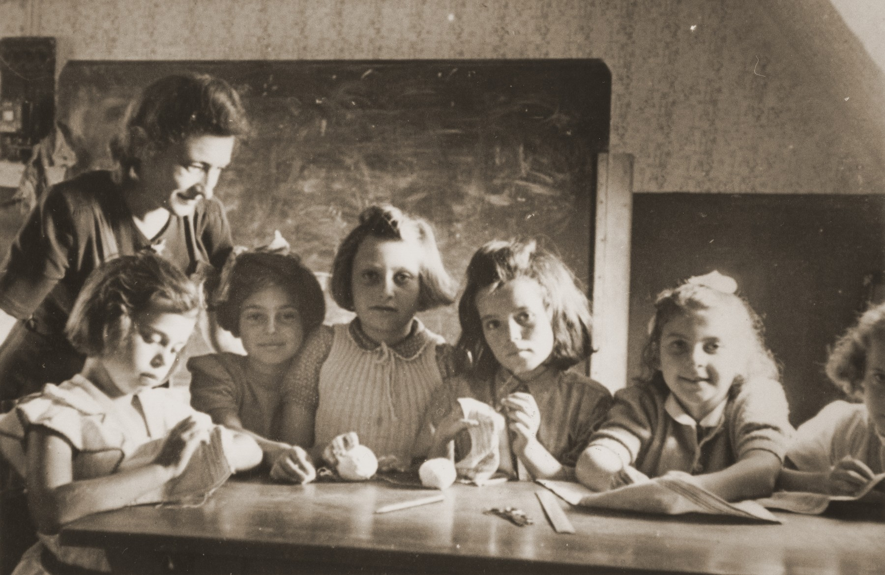Girls learn to sew in a classroom at the Neu Freimann displaced persons camp.  Pictured in the center is Ida (Judith) Stern,  Also pictured are probably Rita Pazenski (far right) and Shulamis (or Shulamit, 4th from right)