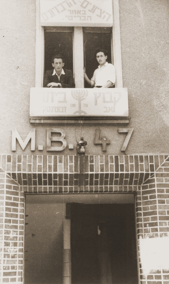 Two Jewish displaced persons look out the windows of the Betar headquarters in the Bergen-Belsen DP camp.  Pictured on the right is Israel Zaks.