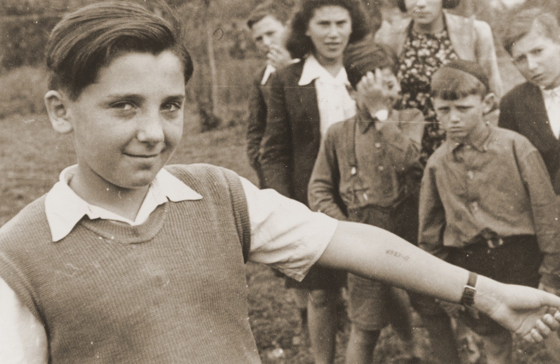 A boy displays the tattooed number on his arm to the photographer, while other children at the Neu Freimann displaced persons camp look on.