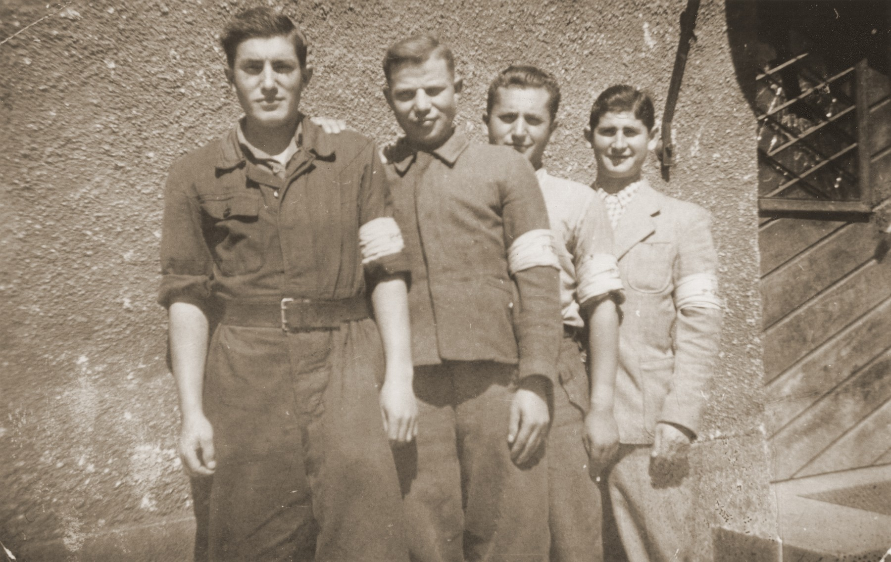 Four Jewish policemen pose wearing armbands in the Landsberg displaced persons camp.    Szmuel Silbiger is pictured on the far left.