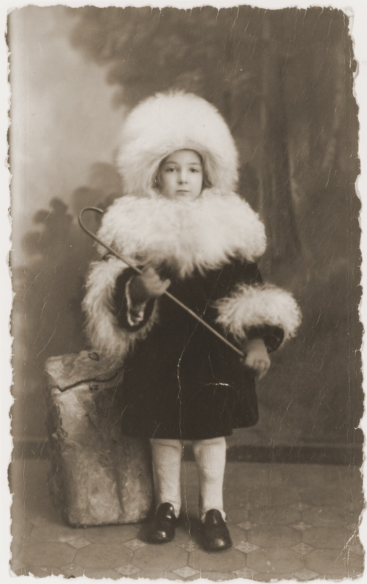 Studio portrait of a Jewish child from Warsaw dressed up in a fur hat and collar.  Pictured is Rivka Radzinski.