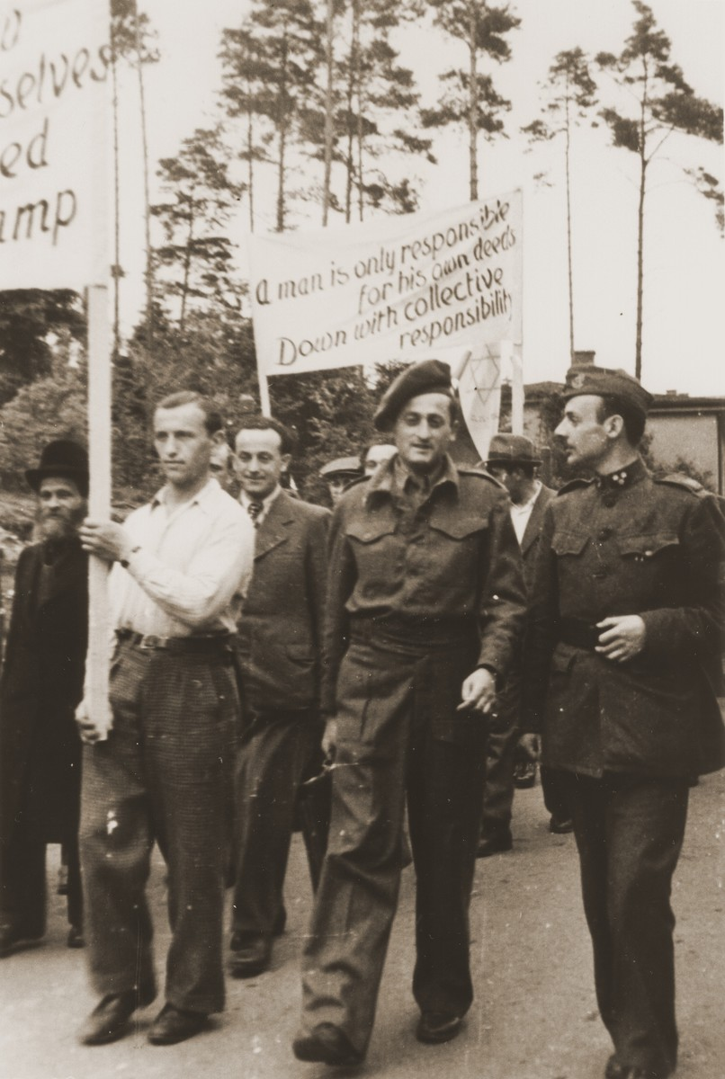 British soldiers walk next to DP protesters at the first Zionist demonstration at the Bergen-Belsen displaced persons camp.
