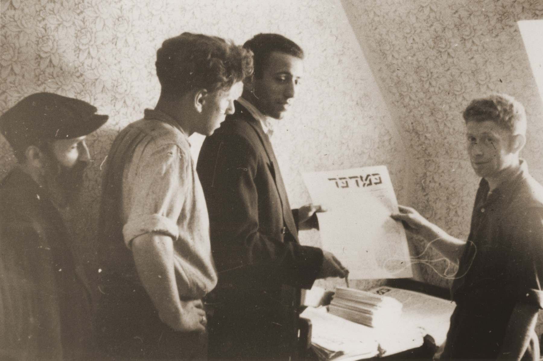 Jewish DPs working in the publications office of the Neu Freimann displaced persons camp hold up the latest issue of the Bamidbar [In the Wilderness] newspaper.