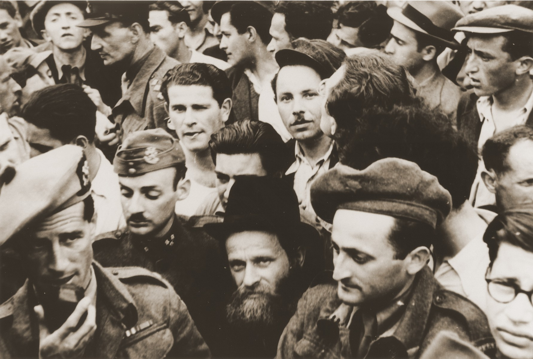 A crowd of Jewish DPs stand behind British soldiers at a ceremony or demonstration in the Bergen-Belsen displaced persons camp.  Rabbi Helfgott is pictured in uniform in the foreground at the right.