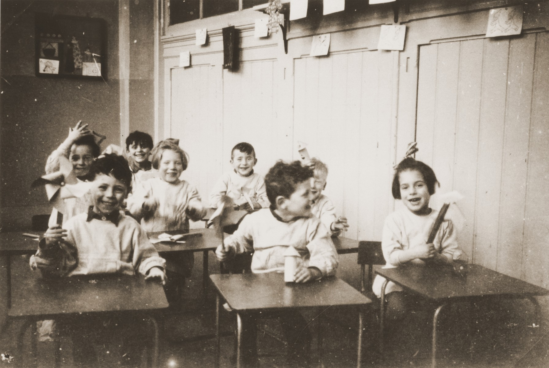 Young Jewish children sit at tables in the childcare center at the Joodsche Schouwburg in the Amsterdam Jewish quarter.