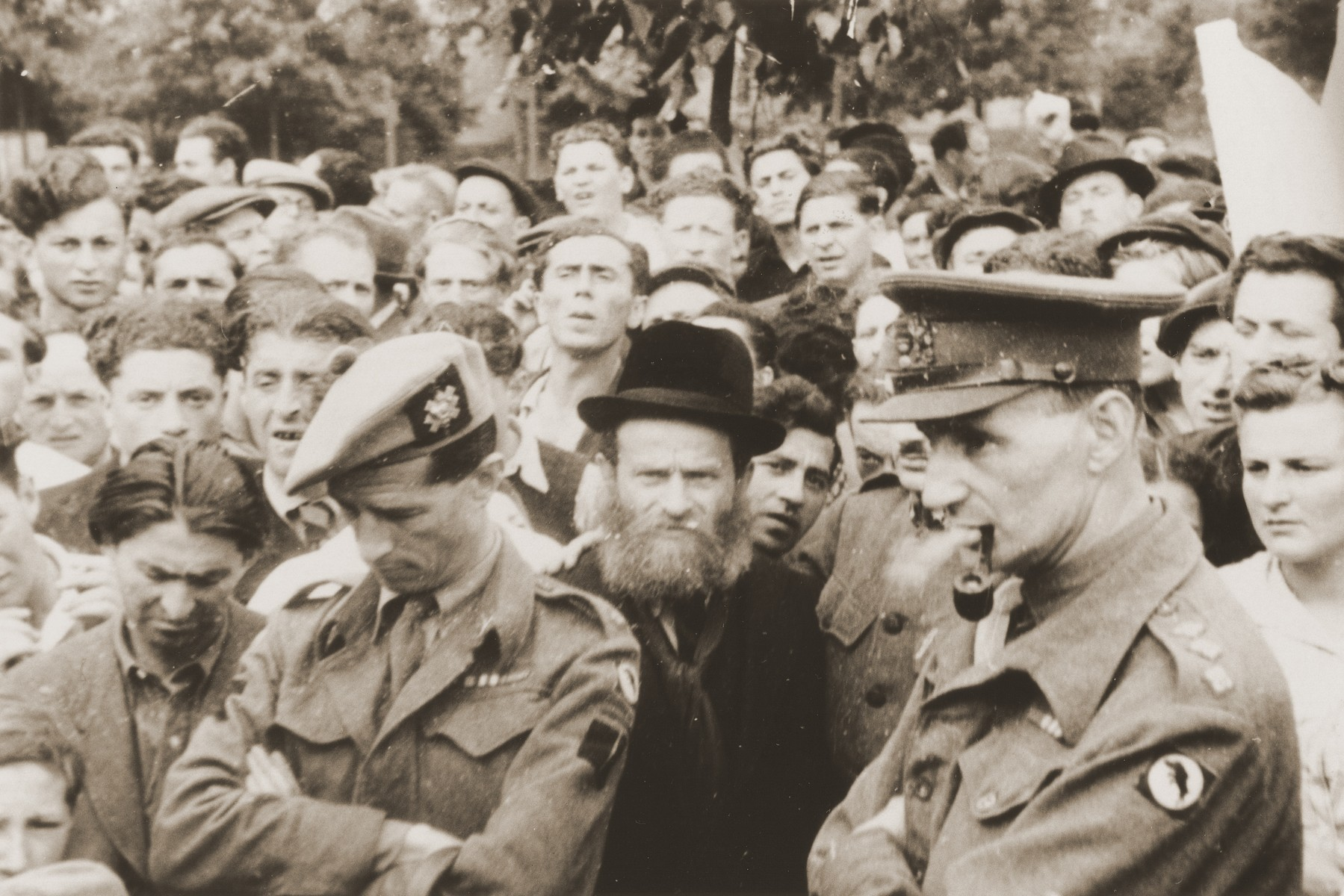 A crowd of Jewish DPs stand behind British soldiers at a ceremony or demonstration in the Bergen-Belsen displaced persons camp.