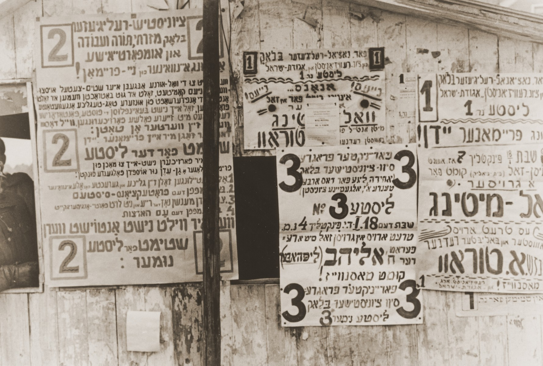 Campaign posters posted on an outdoor bulletin board in the Neu Freimann displaced persons camp.