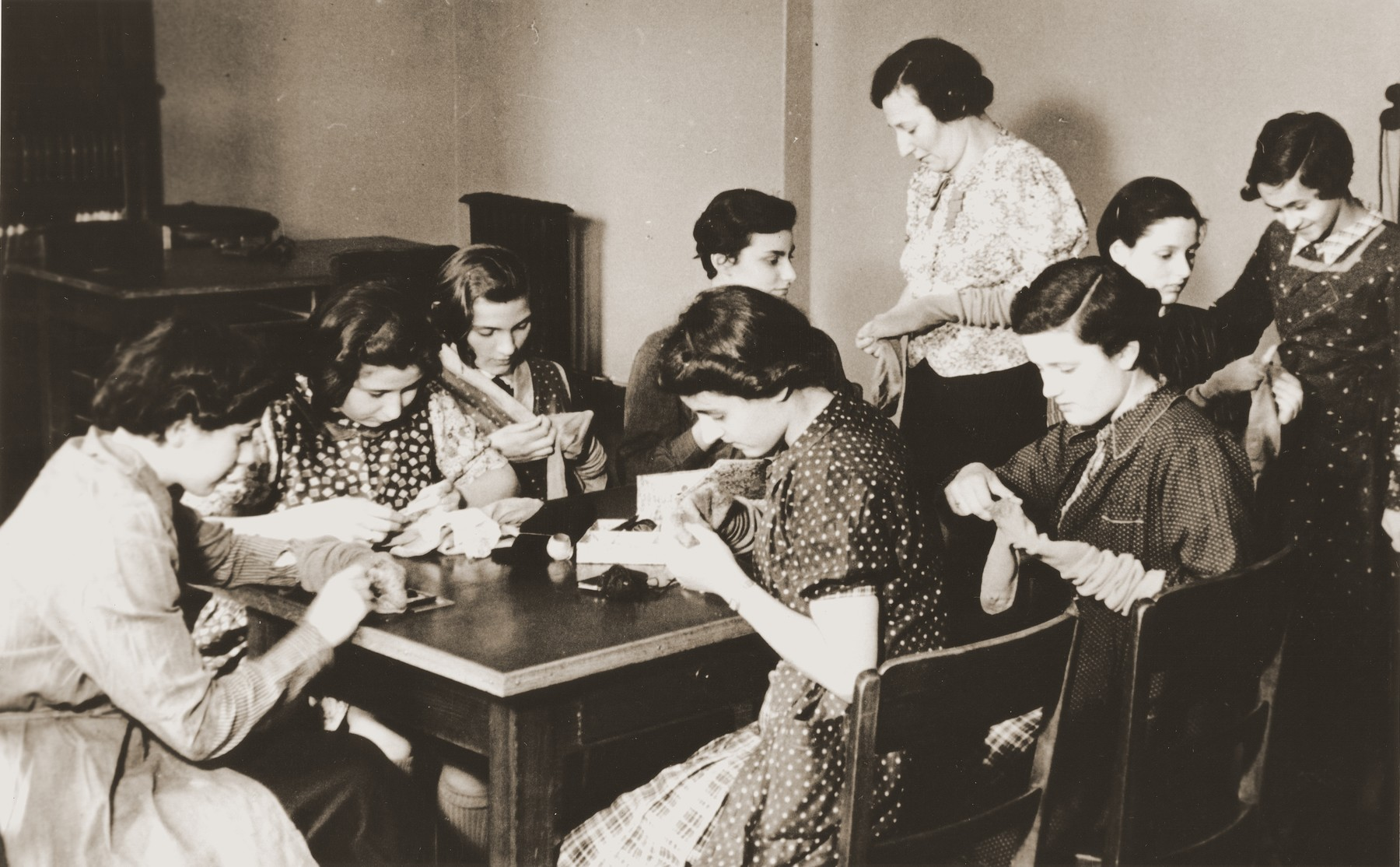 Teenage girls darn socks for the boys of the Baruch Auerbach Jewish orphanage in Berlin.  Margot Peretz is pictured in the front, right.
