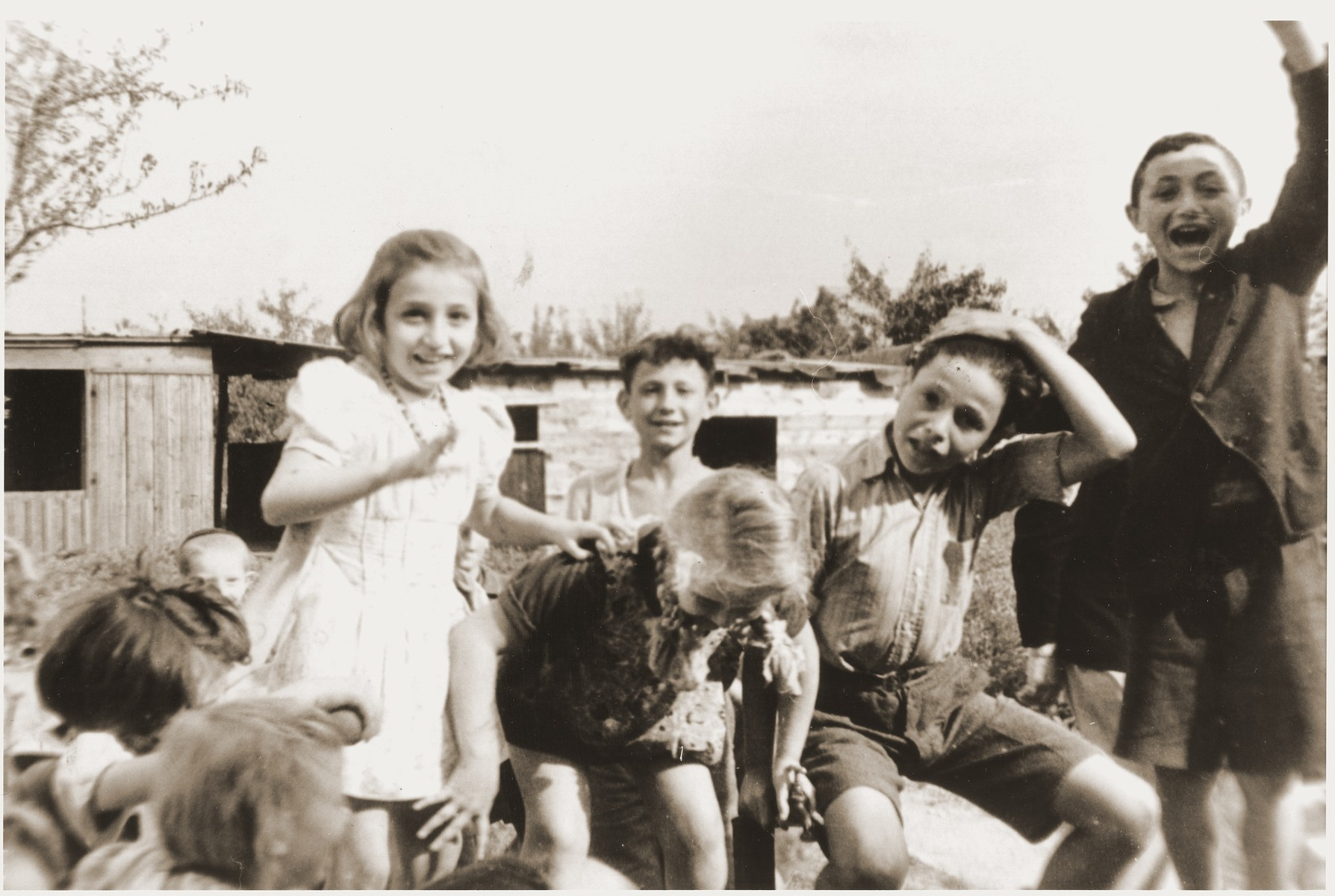 Children play outside in the Neu Freimann displaced persons camp.  Pictured on the far right is Nachman Aaron Elster.