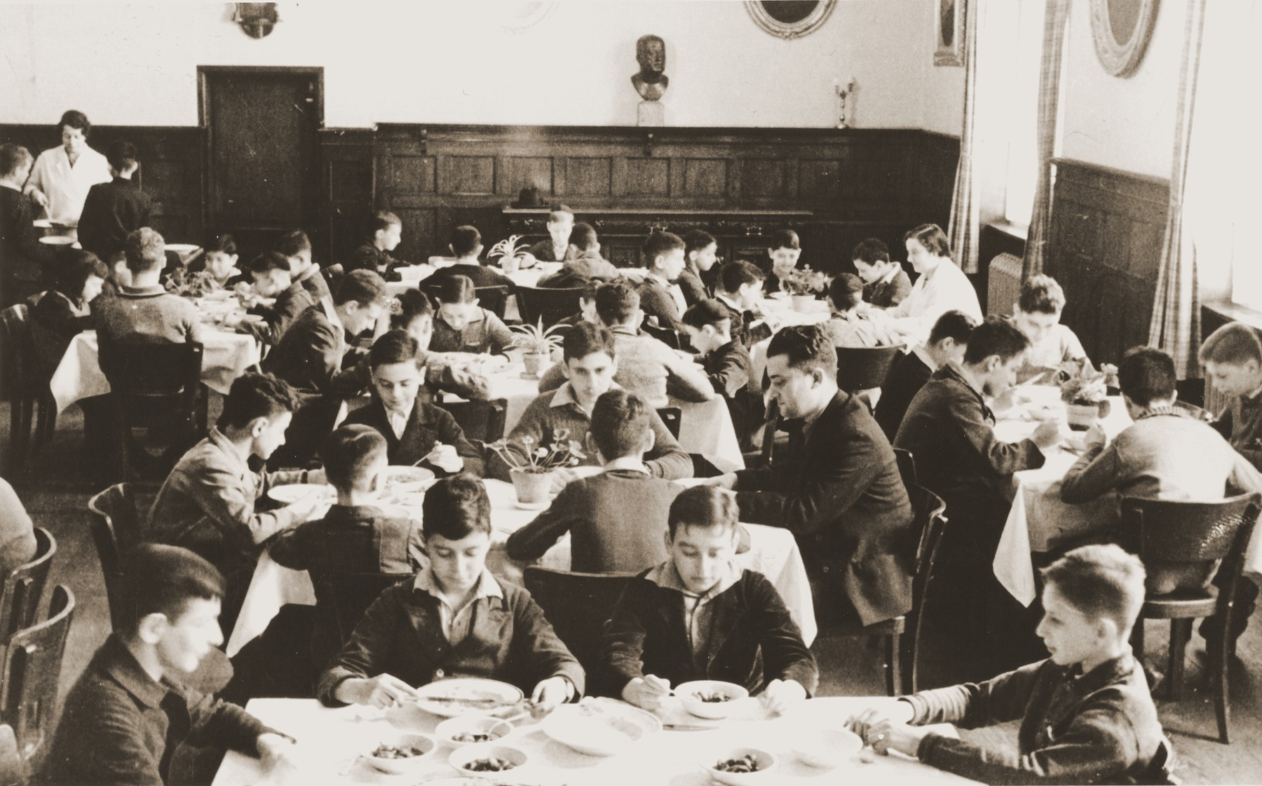 The children eat a meal in the dining room of the Baruch Auerbach Jewish orphanage in Berlin.