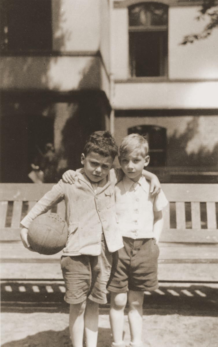 Two young boys pose with a ball in the yard of the Baruch Auerbach Jewish orphanage in Berlin.    The child on the right is Ralph Moratz.  On the left is Wolfgang Grajonca (later Bill Graham).