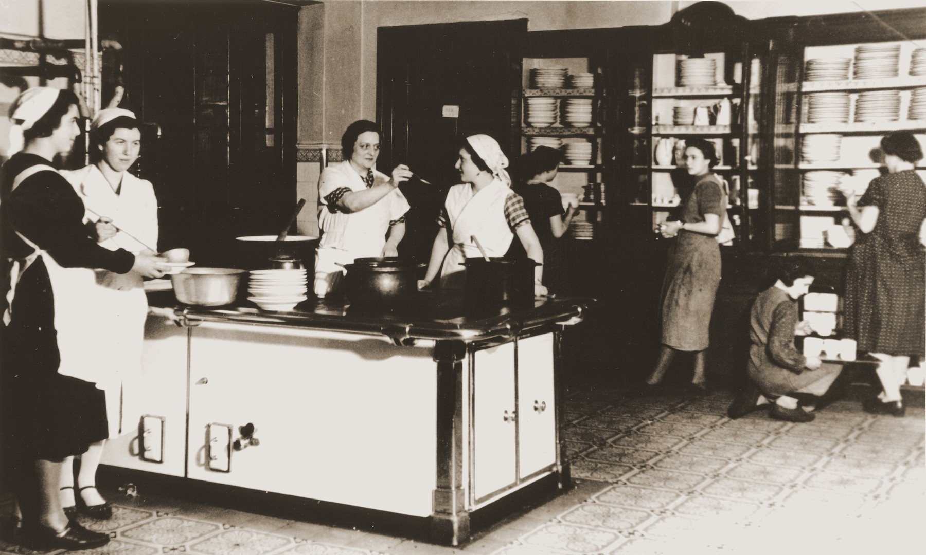 The cooks and kitchen staff at the Baruch Auerbach Jewish orphanage in Berlin prepare a meal.