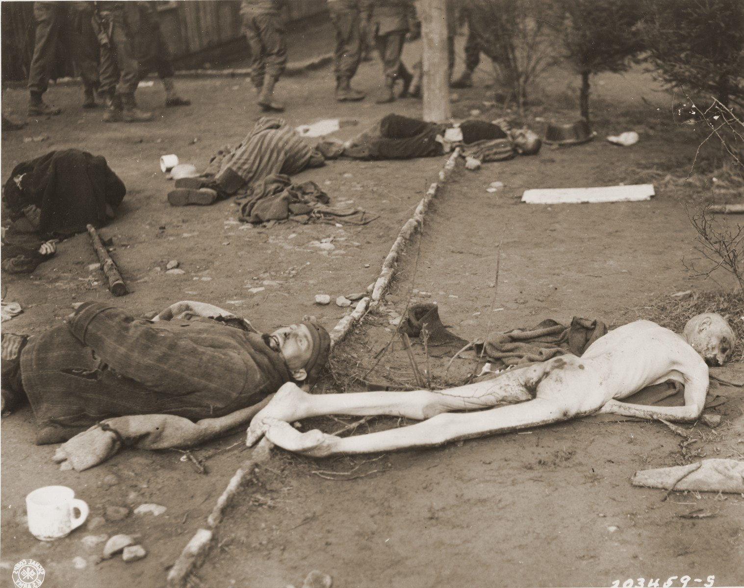 American soldiers walk past corpses strewn upon the ground in Ohrdruf.