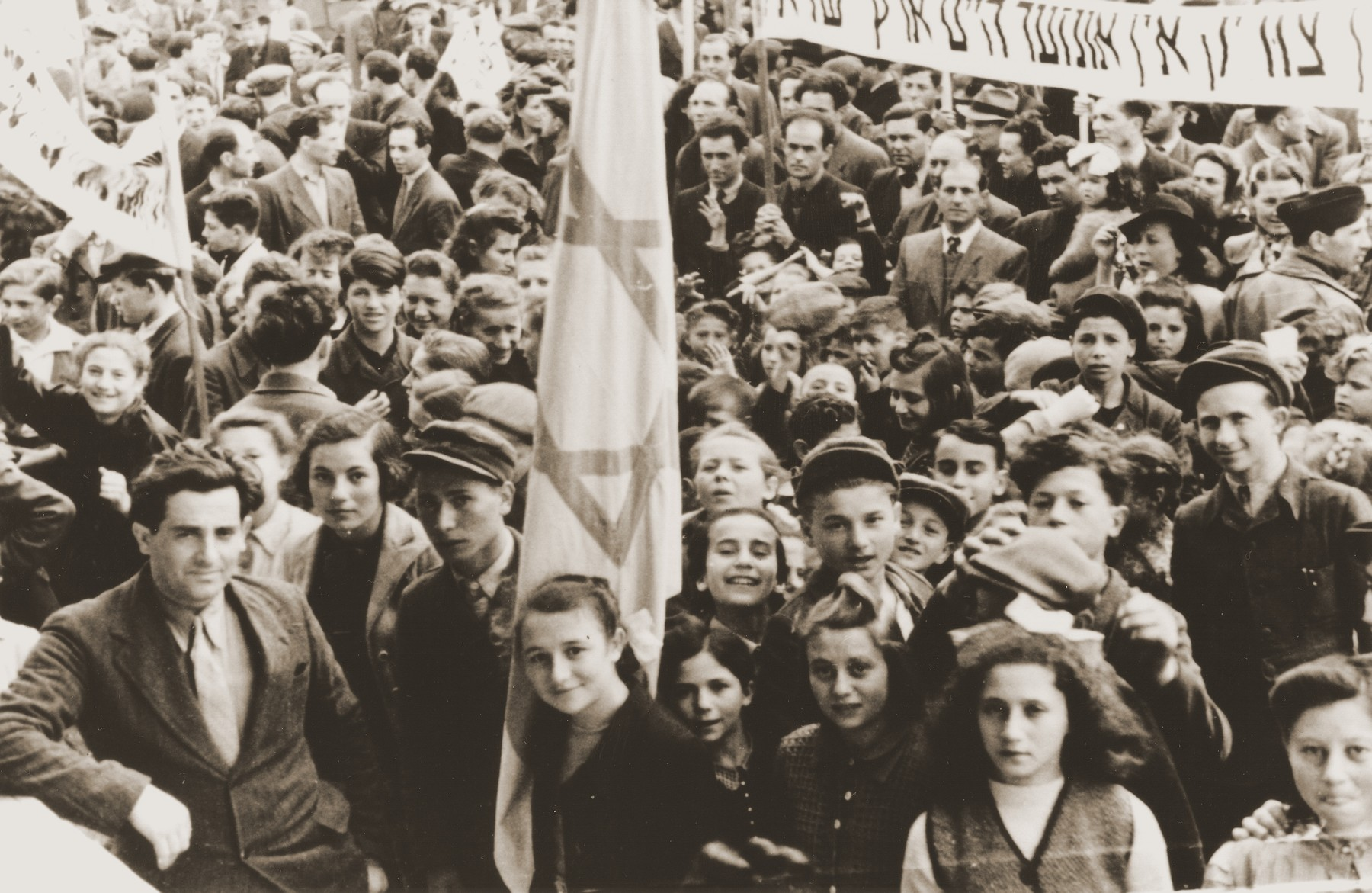 """Zionist demonstration in the Neu Freimann displaced persons camp.   The large banner on the right reads """"We want to go to our homes in the Land of Israel.""""  Pictured in the lower left-hand corner is Morris Sorid."""