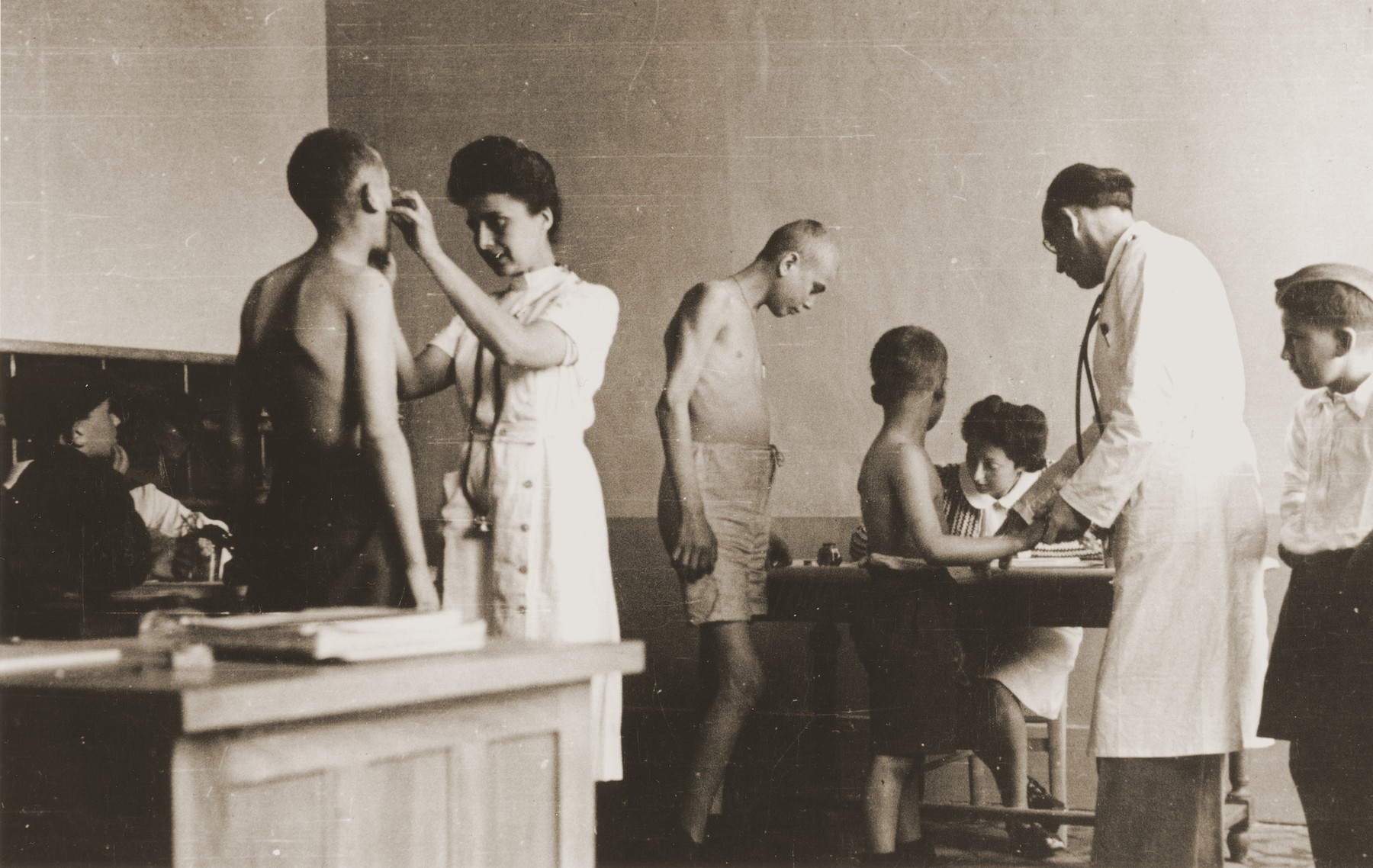 Children liberated at Buchenwald are examined by medical personnel.    Pictured on the far right is Salek Finkelstein.