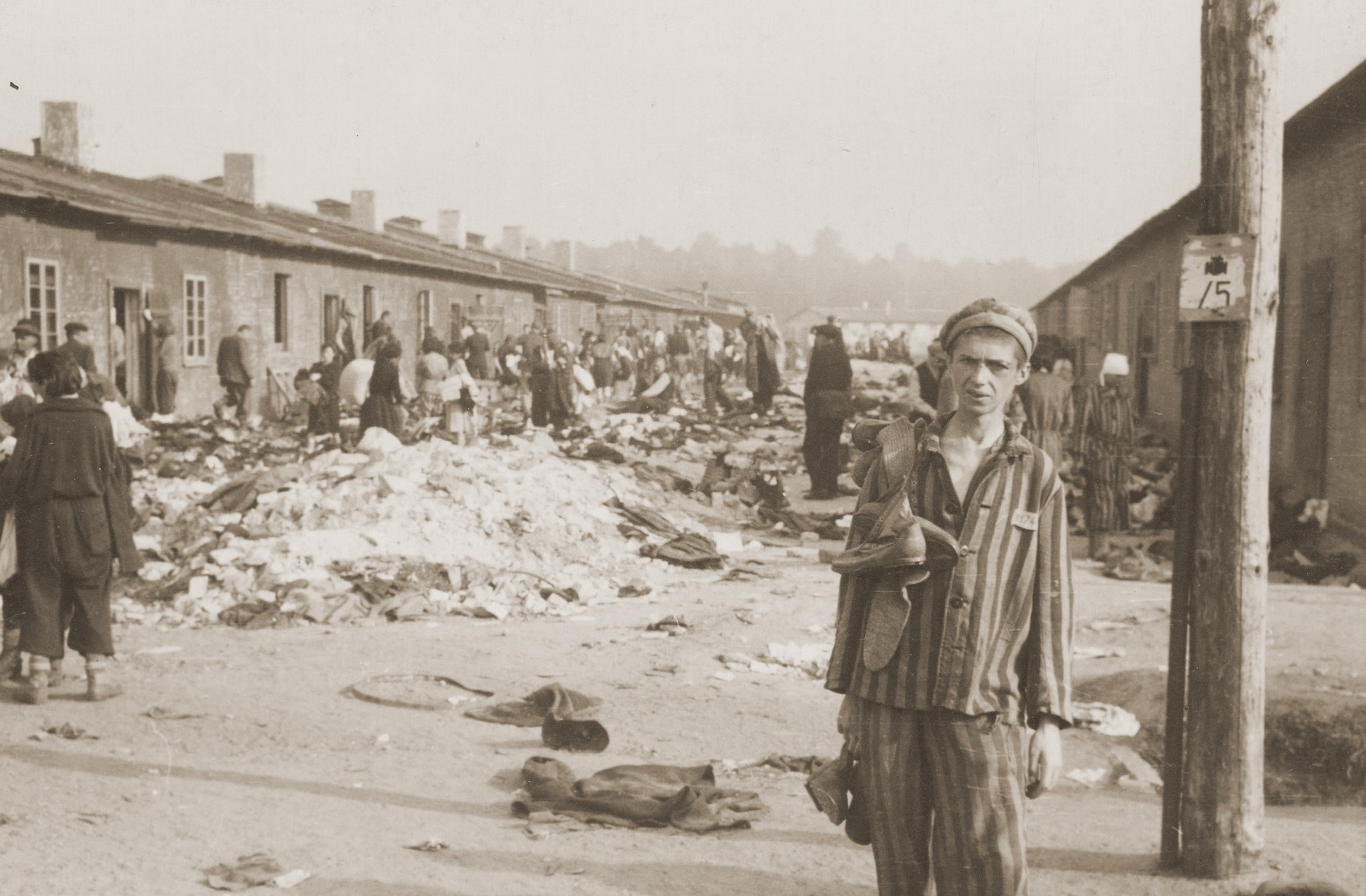 Survivors in Bergen-Belsen wander outside the barracks.