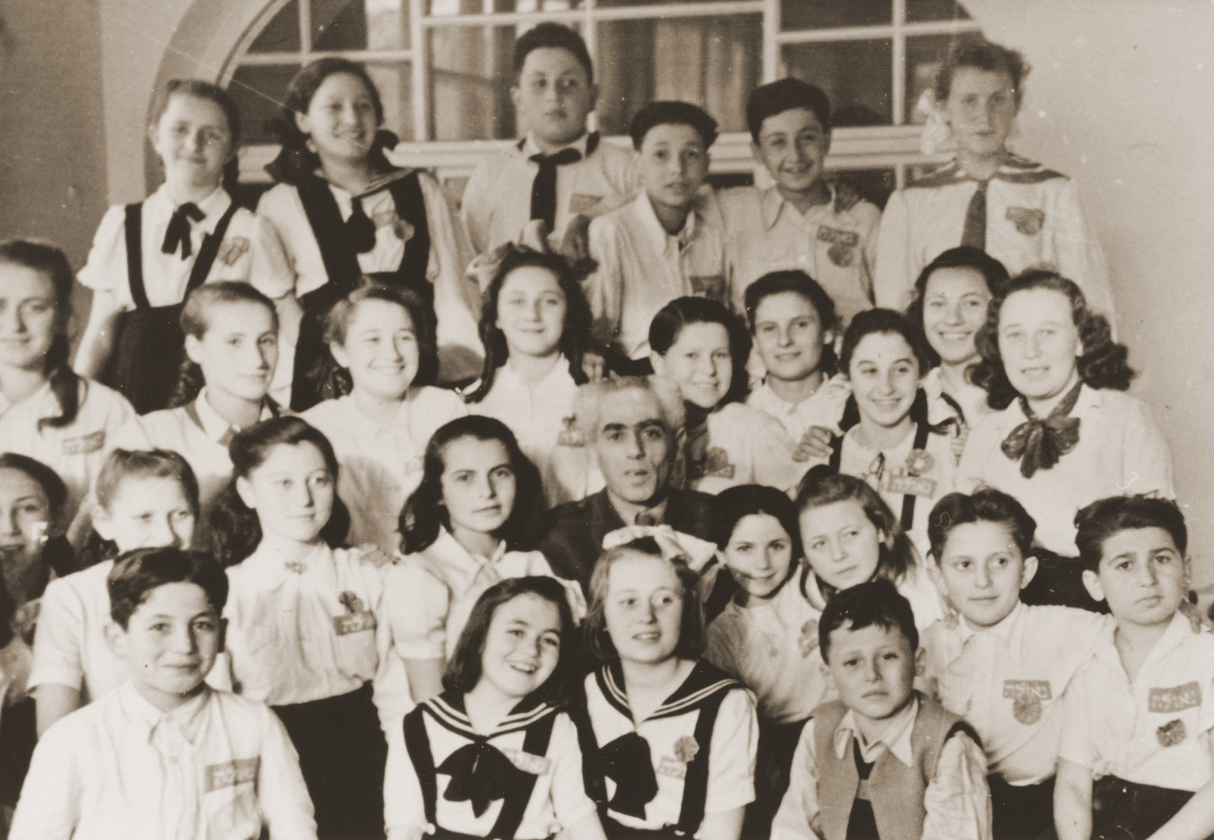 """Group portrait of children in the Neu Freimann displaced persons camp.    The badge on their shirts reads """"Geulah"""" (redemption)."""