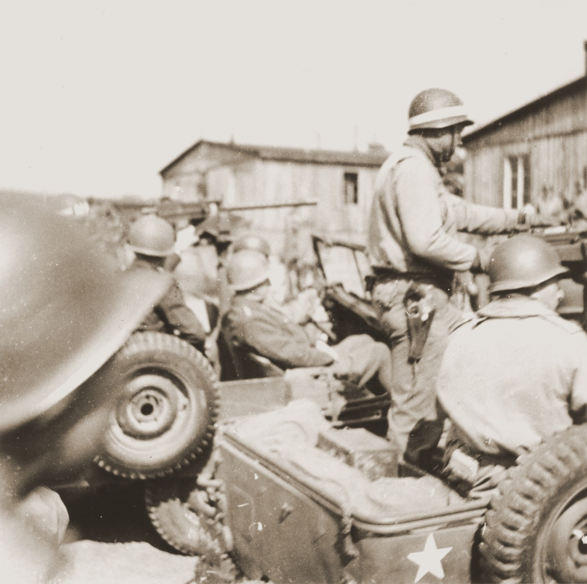 General George S. Patton (seated in the middle jeep) arrives by jeep at the newly liberated Ohrdruf concentration camp in the company of a large group of American troops.