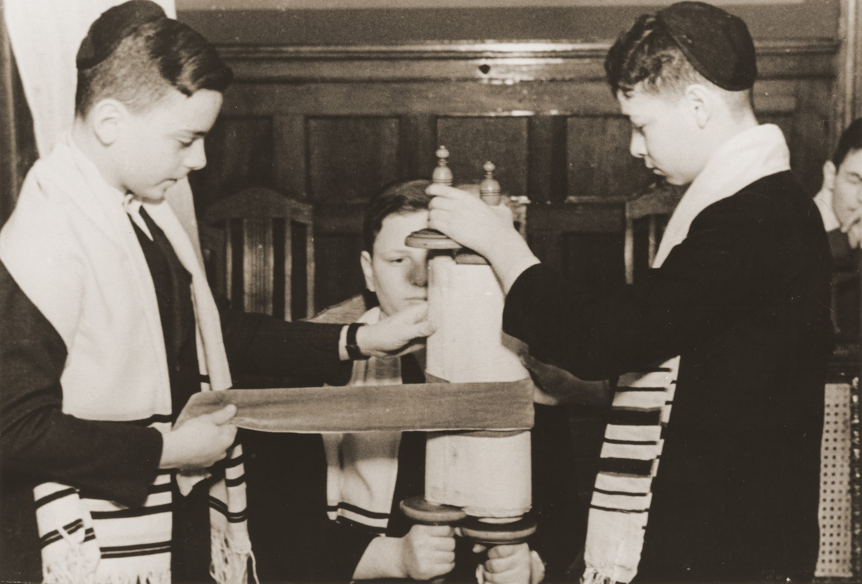 Three boys wrap a small Torah scroll during a service at the synagogue of the Baruch Auerbach Jewish orphanage in Berlin.