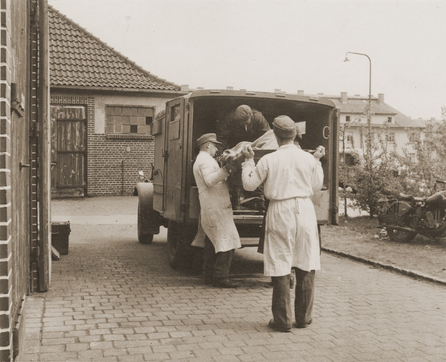 British medical personnel evacuate a survivor by ambulance from the Bergen-Belsen concentration camp.