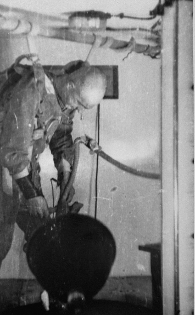A prisoner who has been subjected to low pressure experimentation falls into unconsciousness.  For the benefit of the Luftwaffe, air pressures were created comparable to those found at 15,000 meters in altitude, in an effort to determine how high German pilots could fly and survive.
