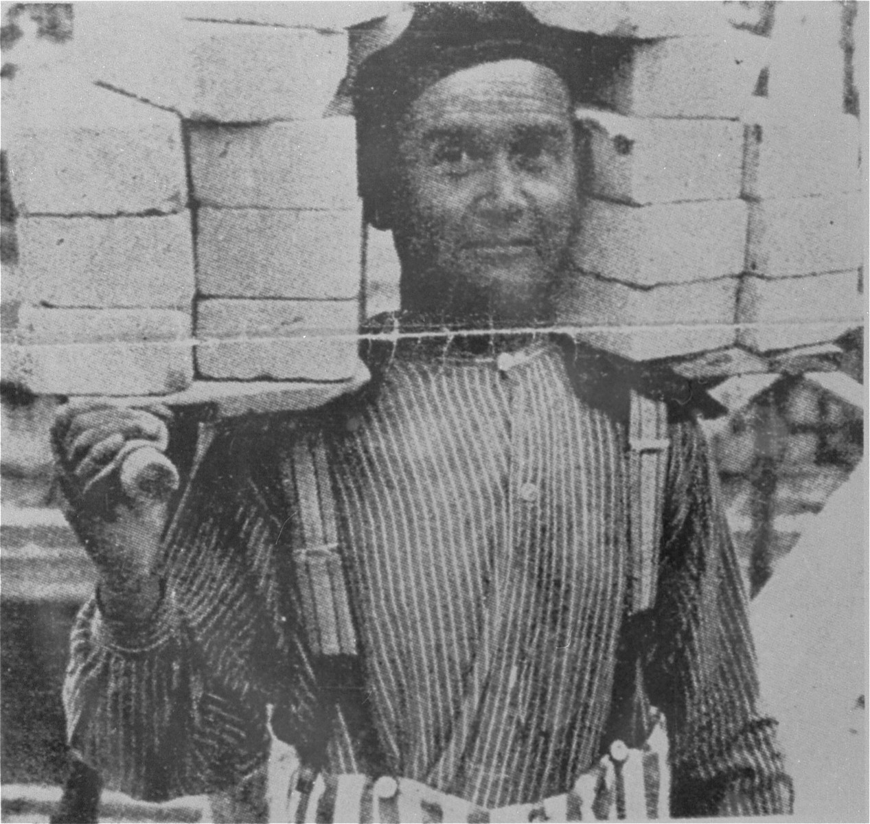 "Propaganda photo of a prisoner in Dachau at forced labor.    The caption which originally appeared with this Nazi propaganda photograph read: ""A load of bricks is lighter then the burden of the crime - appreciation for achievement is taught""."