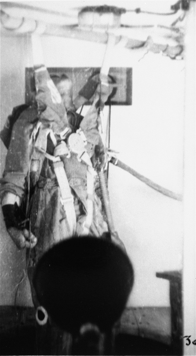 A prisoner in a special chamber who has been subjected to low pressure experimentation falls into unconsciousness.  For the benefit of the Luftwaffe, air pressures were created comparable to those found at 15,000 meters in altitude, in an effort to determine how high German pilots could fly and survive.