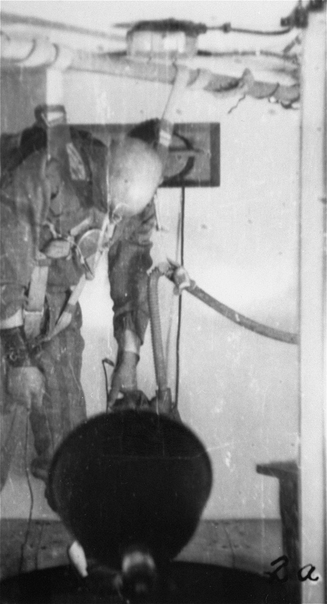 A prisoner in a special chamber who has been subjected to low pressure experimentation falls into unconsciousness.  For the benefit of the Luftwaffe, air pressures were created comparable to those found at 15,000 meters in altitute, in an effort to determine how high German pilots could fly and survive.