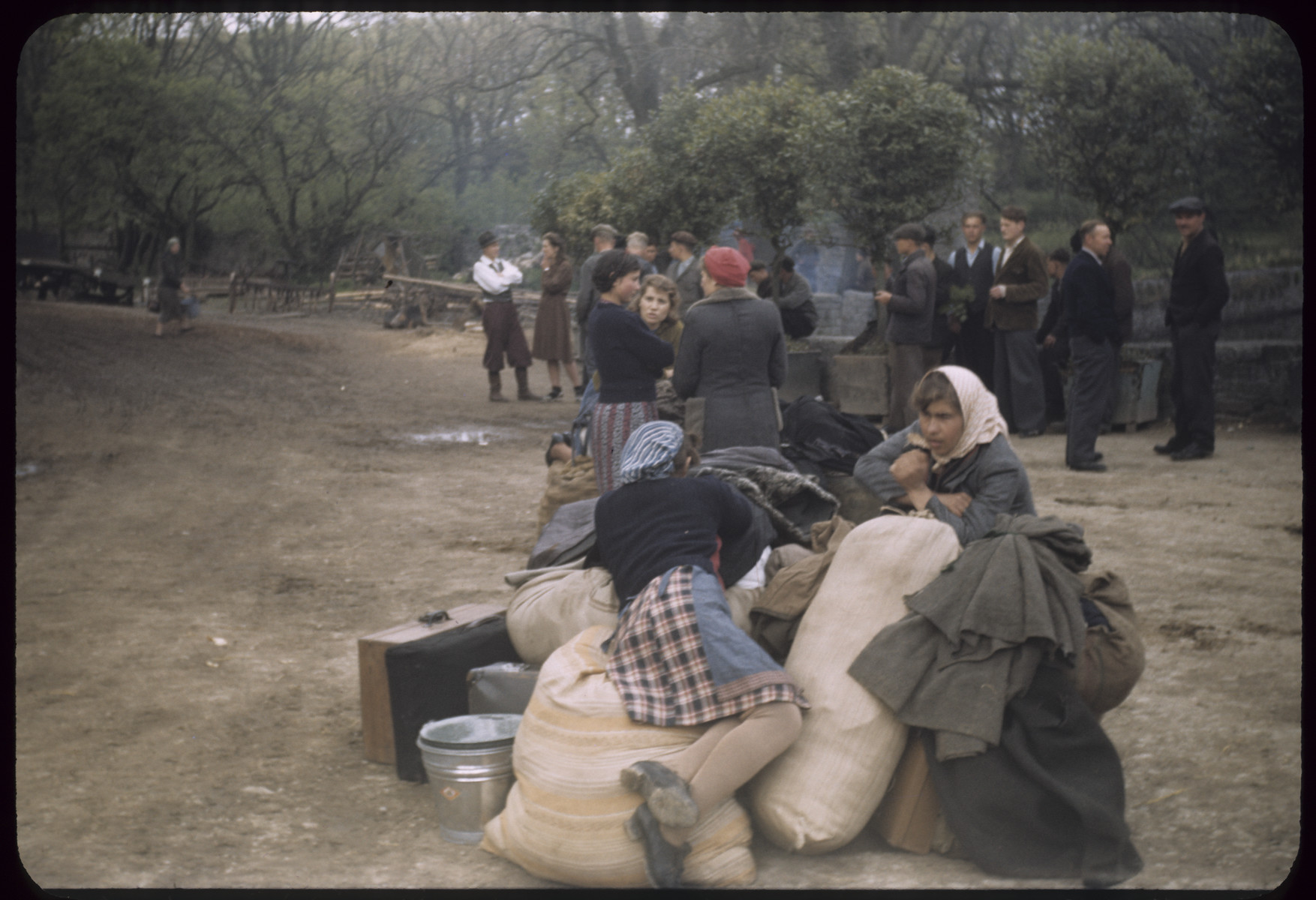 Displaced persons wait next to their suitcases and bundles.
