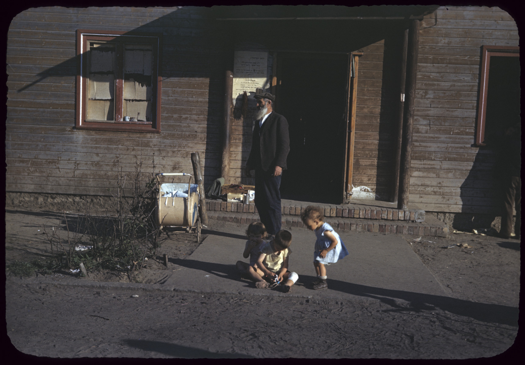 An older man stands in front of the entrance to a buliding in s displaced persons camp, while three young children play with a small toy in front of him.
