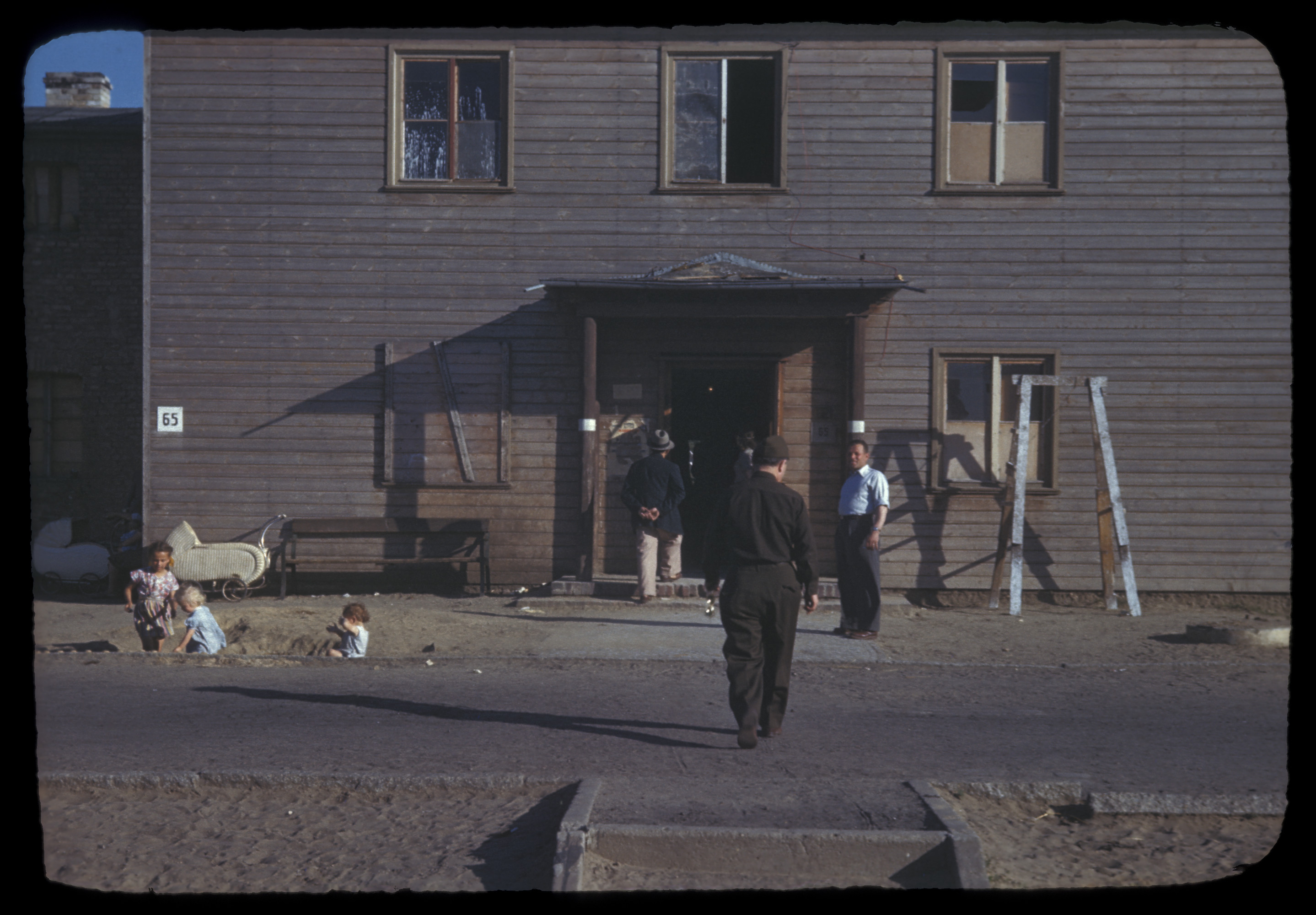 Several men enter a building at a displaced person's camp in Berlin, as young children play along the road.