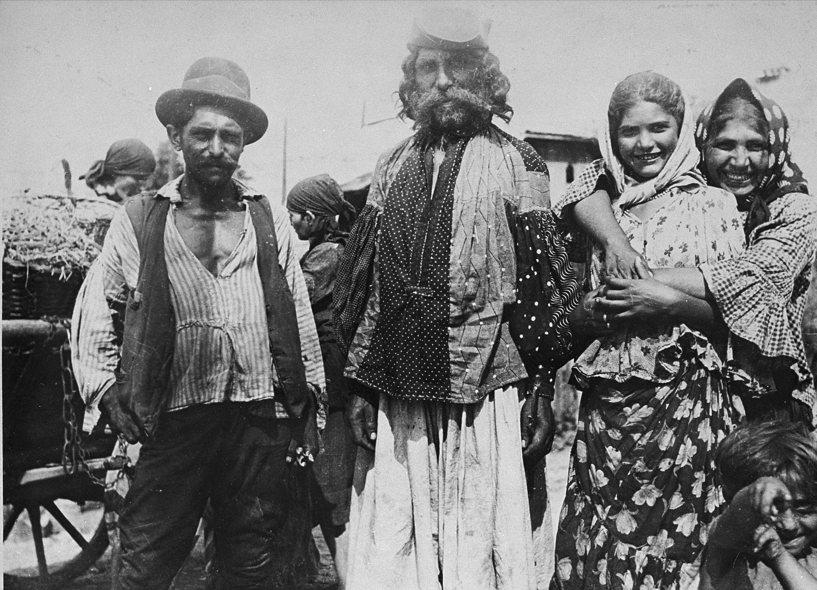 The chief (Vajda) of a Roma tribe iroma stands in the center, flanked by a man and two women.
