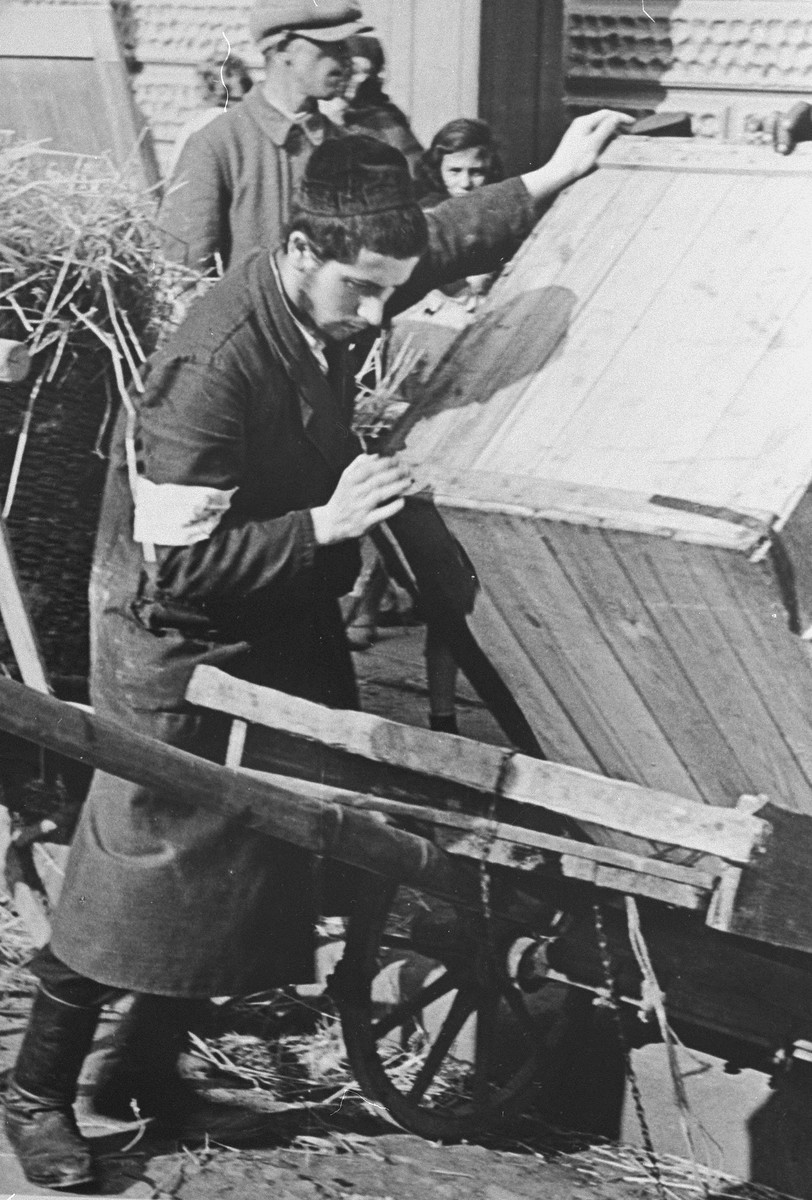 A religious Jewish youth loads a large crate onto a cart in the Krakow ghetto.