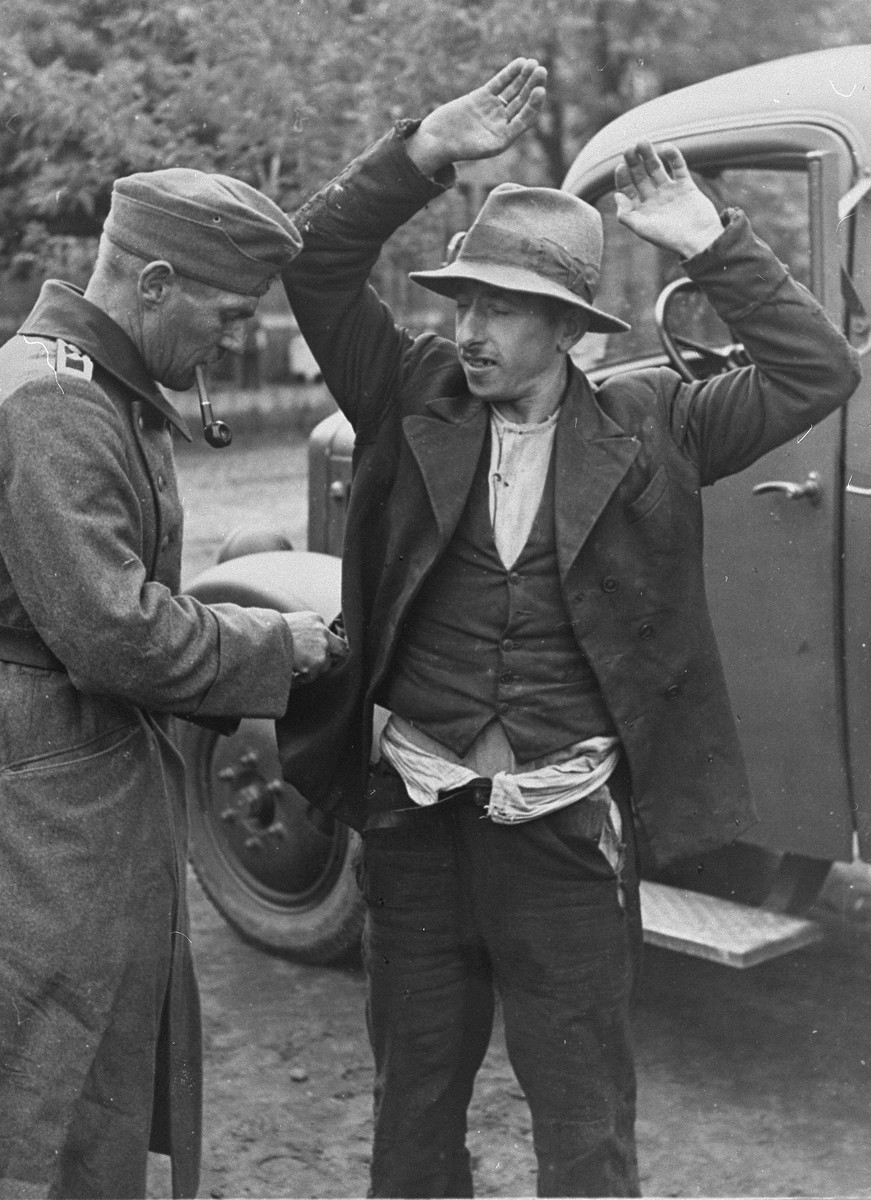 A German soldier searches a Roma (Gypsy) man who is forced to stand with his arms in the air.