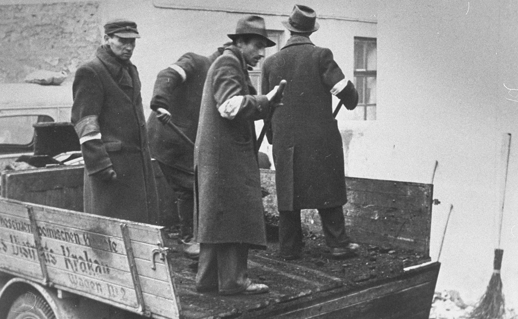 A group of Jewish men wearing armbands, shovel coal off the back of a truck.