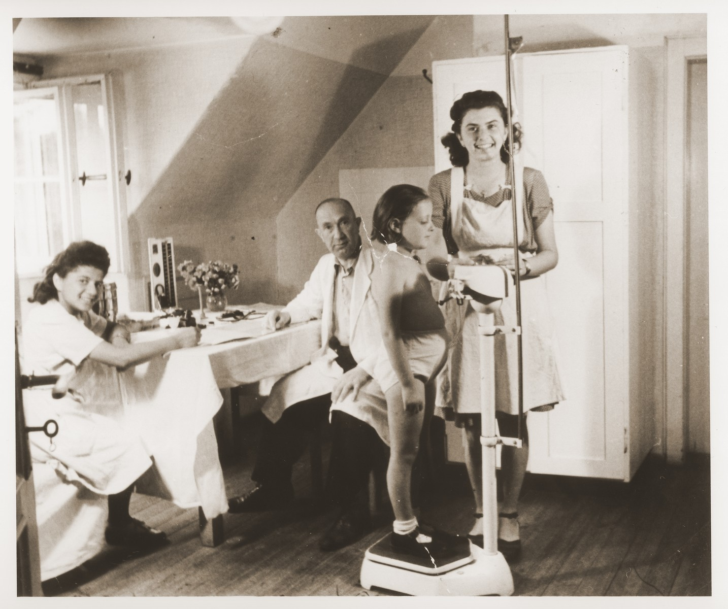 A young girl is weighed at a doctor's office in a sanatorium near Foehrenwald.    Among those pictured are Gisella Lachs Littman (seated at the table) and Kato Roth (standing on the right).