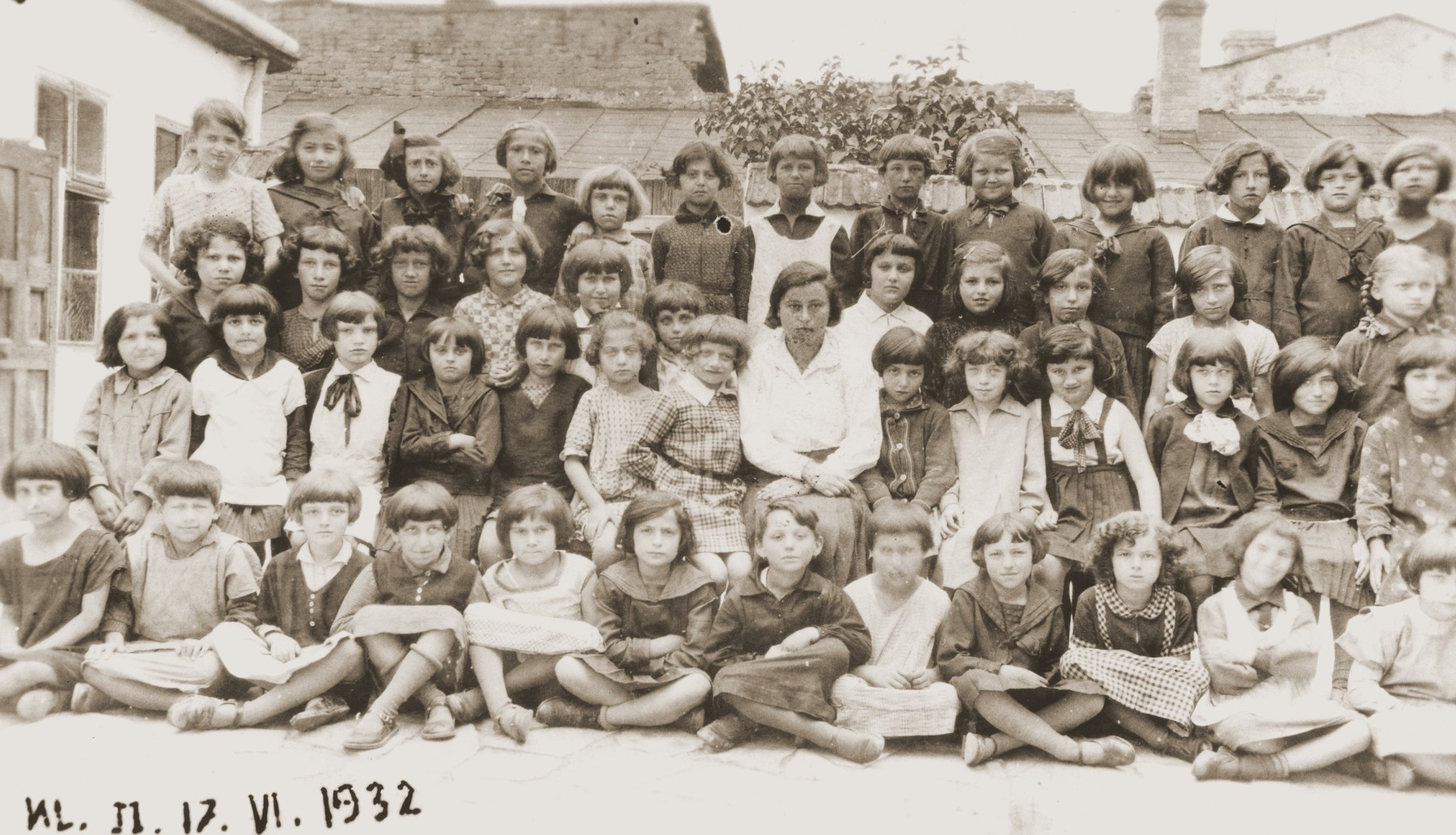 Group portrait of second grade girls at the Zydowska Szkola Powszechna, a private Jewish elementary school in Brody.  Pictured from left to right are: bottom row: Rozia Bojeches, Feuerstein, Achtentuch, Friedman and unknown;  second row: Liberman, Palace, unknown, unknown, Marta Barach, unknown, unknown, Ida Tabask (teacher), Mania Kanczuker, unknown;  third row: Cyla Chari, Bruh, unknown, Sabina Braun, Holzeger, Pepa Frenkel, Mania Federman, Chana Braun, Demb;  top row: Lerner, Esther Braun, unknown, Fruschlinger, Mania Katz, Altman, Lerner, Rabinowitz, unknown, Mania Baras and unknown.