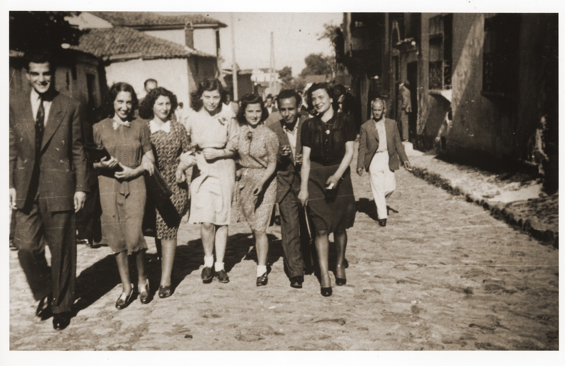 Family and friends walk down Tabaneh Street in the Jewish quarter of Monastir, just  after a wedding (synagogue pictured in the background on the left).  Among those pictured are (left to right) Leon Franco (a cousin of Rachel), Rachel (nee Nahmias) Kornberg, [first name unknown] Pardo, [first name unknown] Shami, Elinor [last name unknown], Moise [last name unknown], and [an unidentified woman].