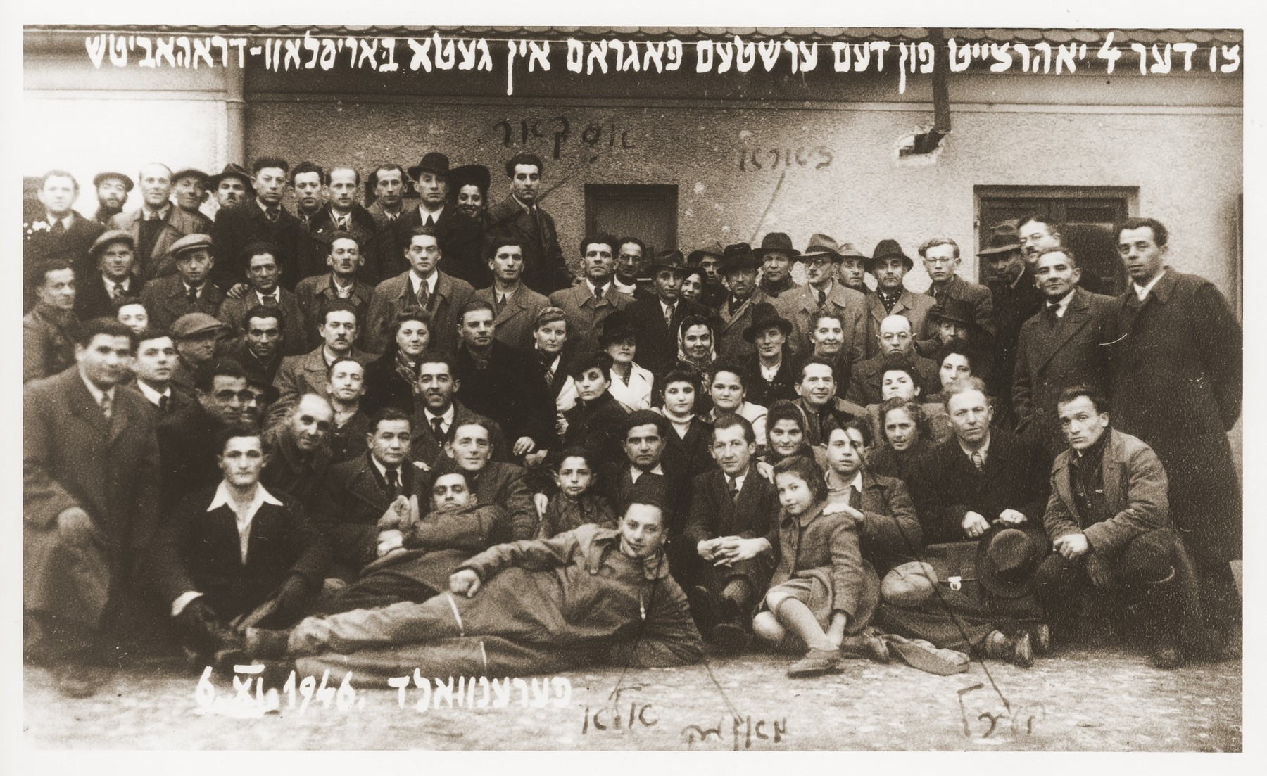 "Group portrait of survivors from Borislov and Drohobycz, who have assembled at the Foehrenwald displaced persons camp to commemorate ""the fourth anniversary of the first pogrom in the Borislov-Drohobycz ghetto.""    Among those pictured are Oskar Littman and the Einsiedler and Herzig families."