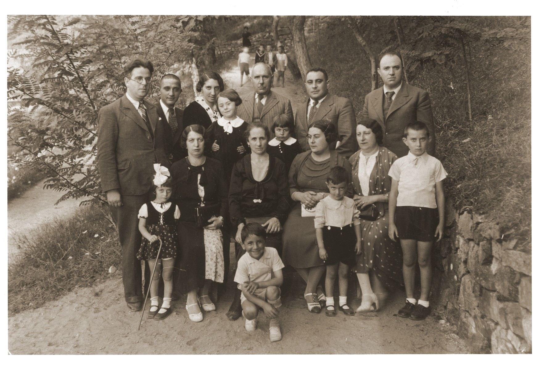 Group portrait of a Jewish family on vacation at Vranjska Banja.    Among those pictured are Jacques Nahmias (standing in back, second from the left), Rachel (nee Nahmias) Kornberg, (standing in back, third from the left), Avram Nahmias (standing in back, third from the right), Mato (nee Franco) Nahmias (seated, second from the left), and Victor Nahmias (front, kneeling).