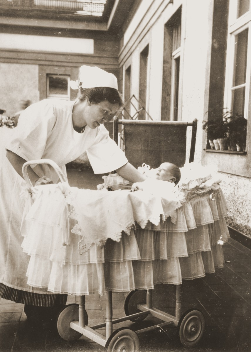 A German nursemaid lays the infant Inge Marx in her bassinet.