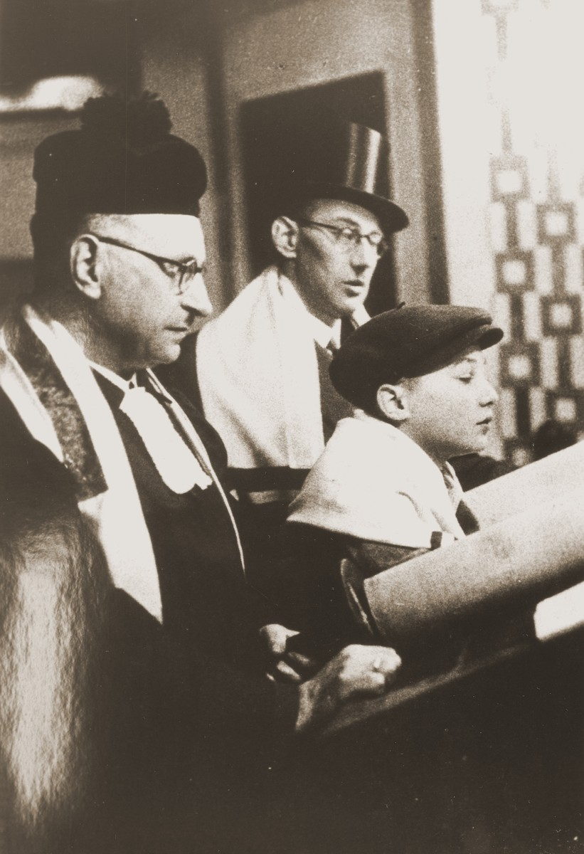 Siegbert Levy, flanked by his father (right) and Cantor Hermann Levy, reads from the Torah scroll during his bar mitzvah at the liberal Zerrennerstrasse synagogue in Pforzheim.