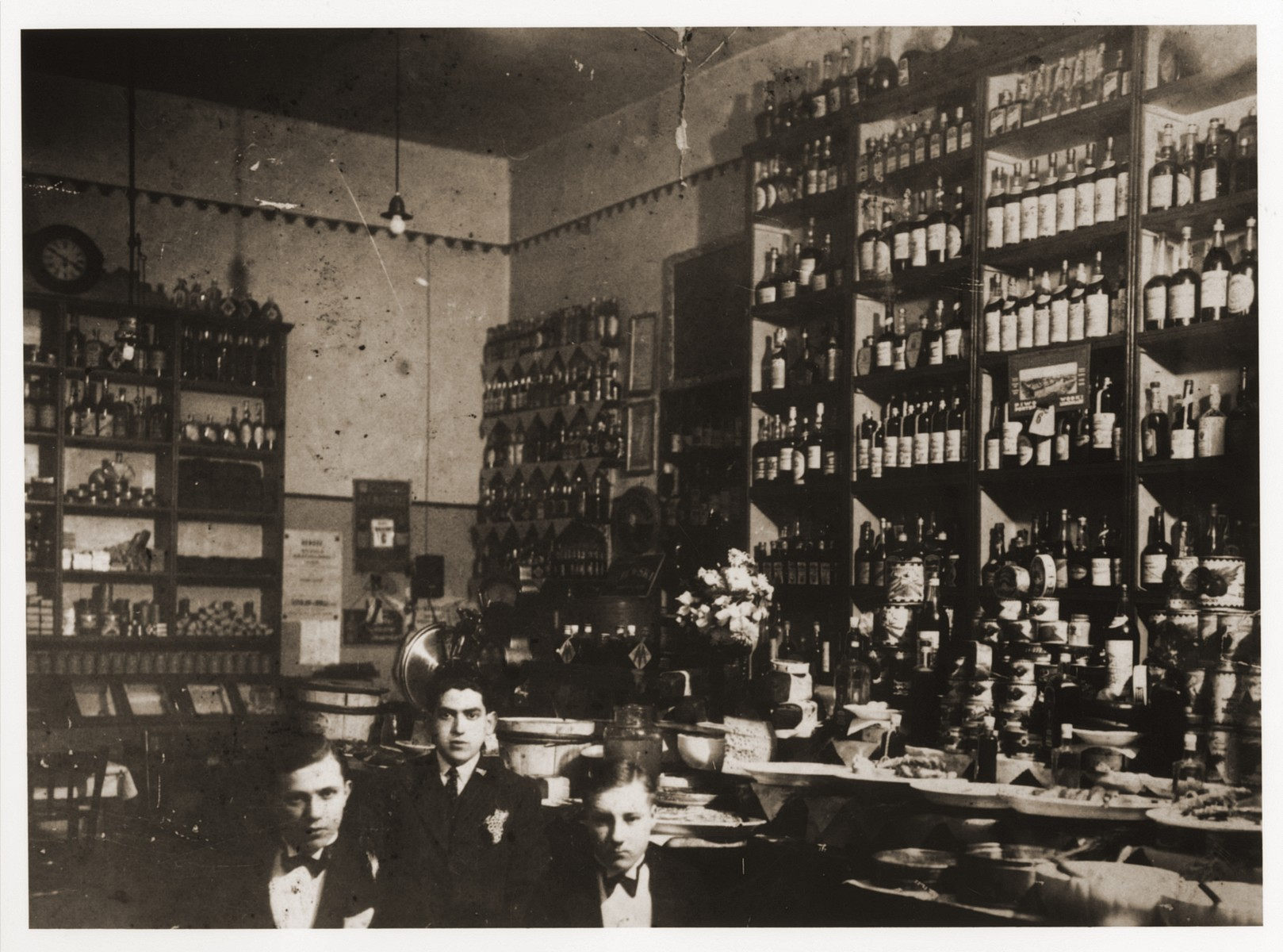 Izio Littman (center) and two friends pose in a liquor store in Drohobycz, Poland.