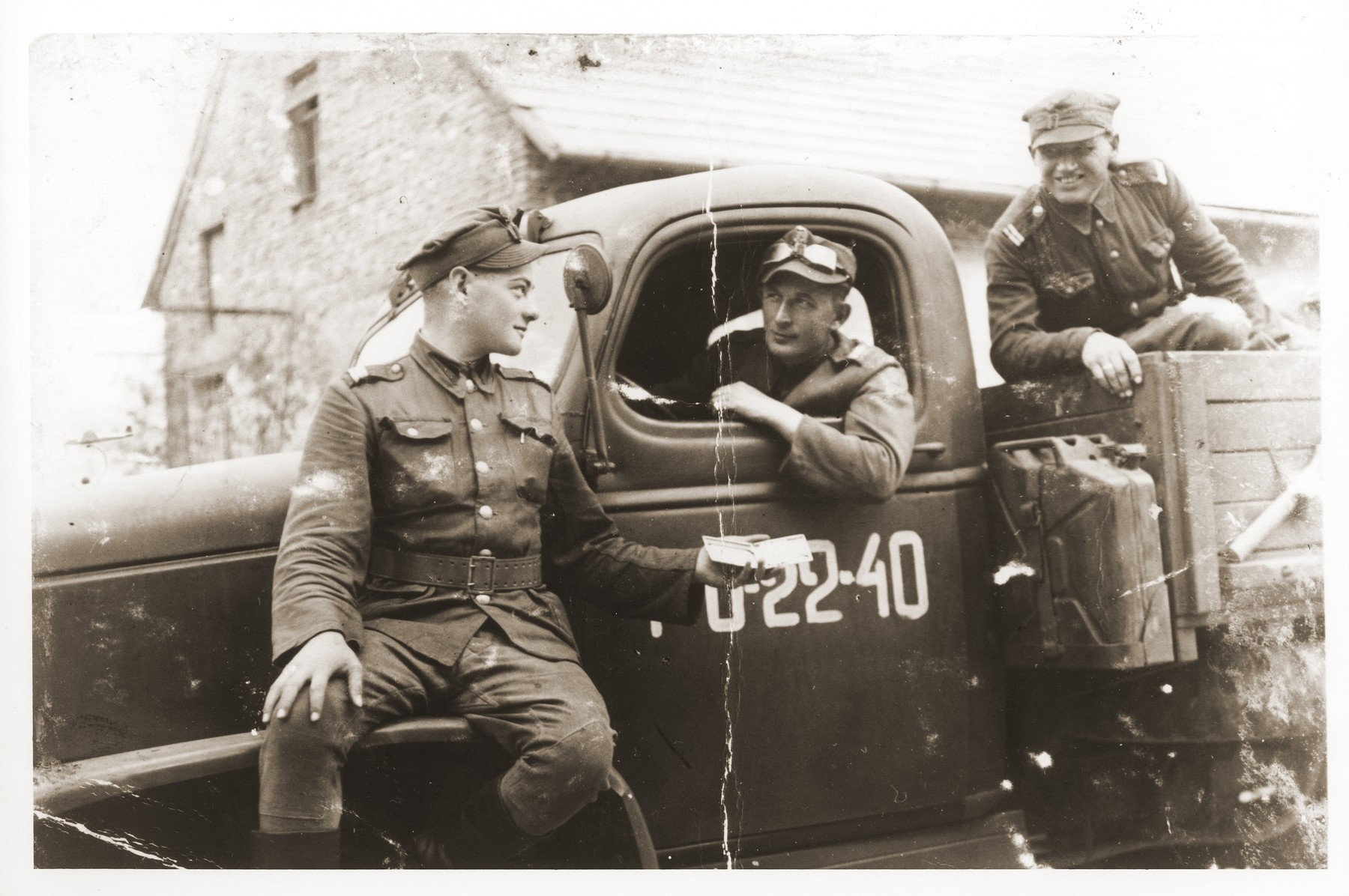 Oskar Littman (left) poses with two members of his Polish army unit in front of their truck.