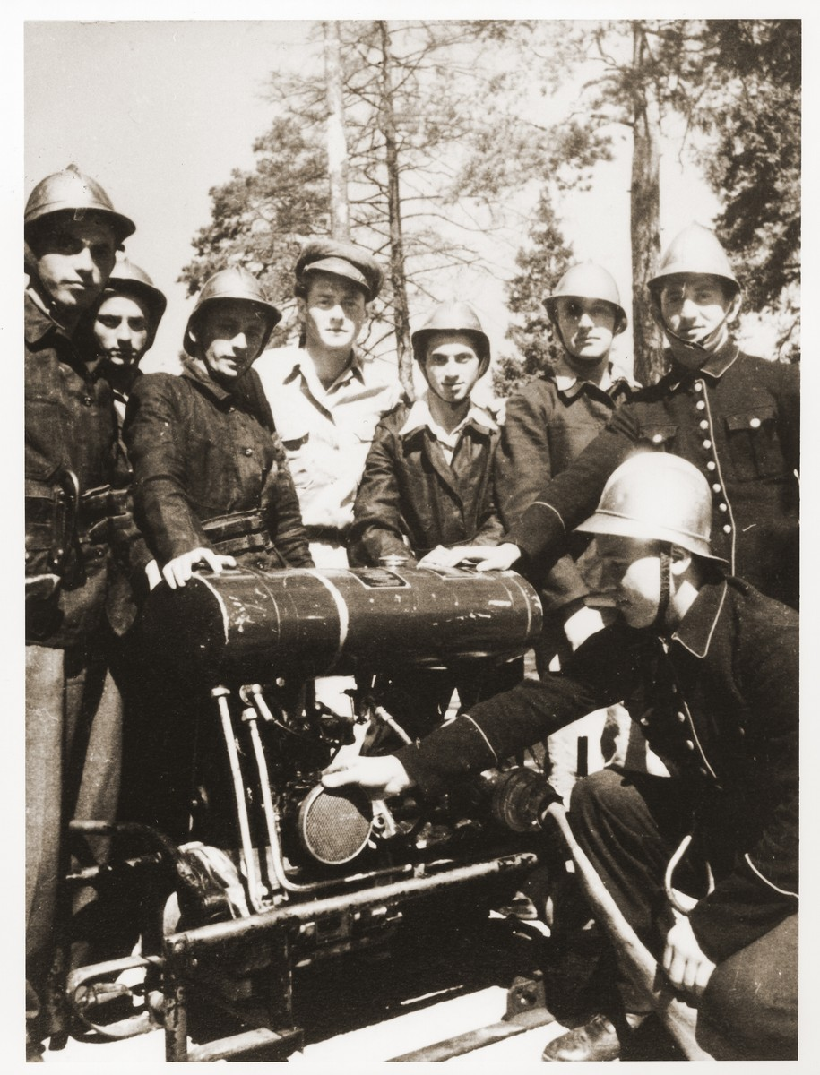 Members of the Foehrenwald displaced persons camp fire department pose outside with a piece of equipment.  Oskar Littman, the fire chief, is pictured in the center, wearing a soft cap and light shirt. Third from the right, in the back row, is Josef Zolna.
