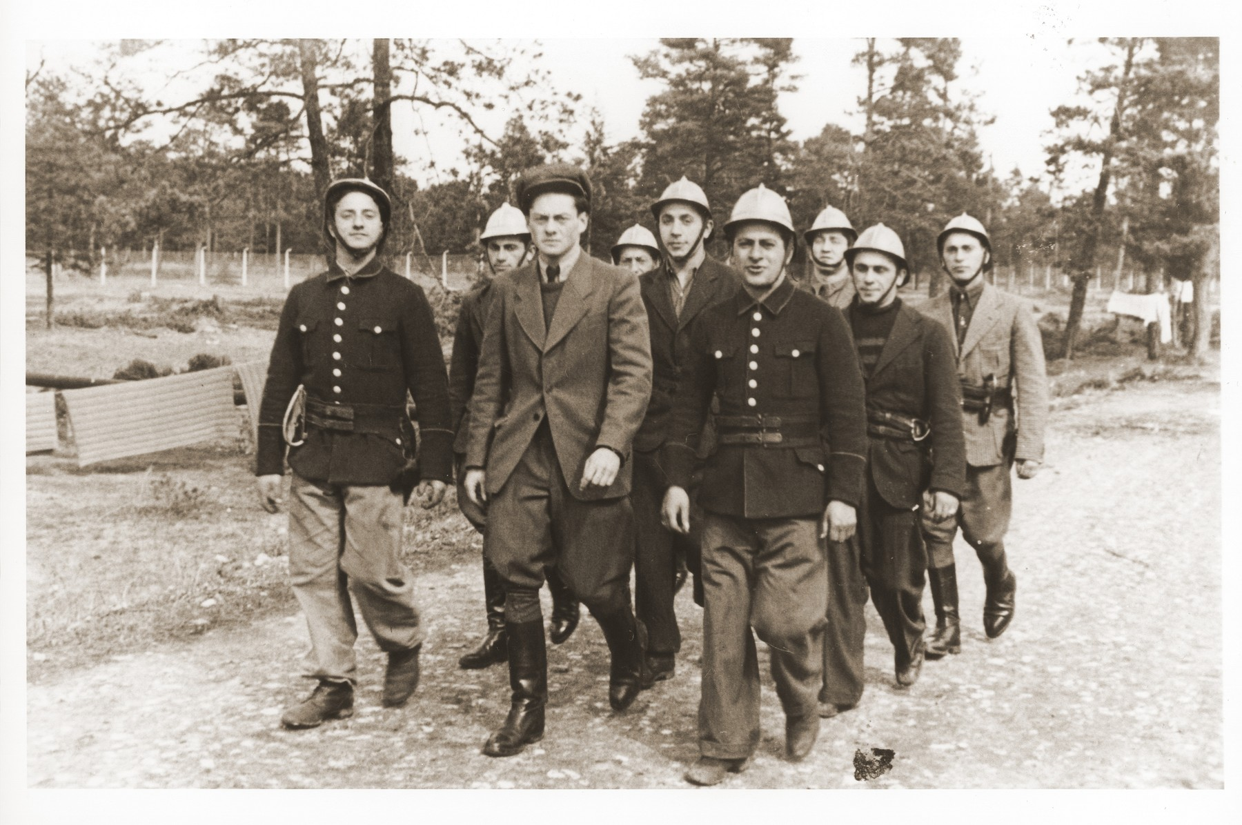 Members of the Foehrenwald displaced persons camp fire department march along a road in the camp.  Oskar Littman, the fire chief, is pictured in the center wearing a soft cap.