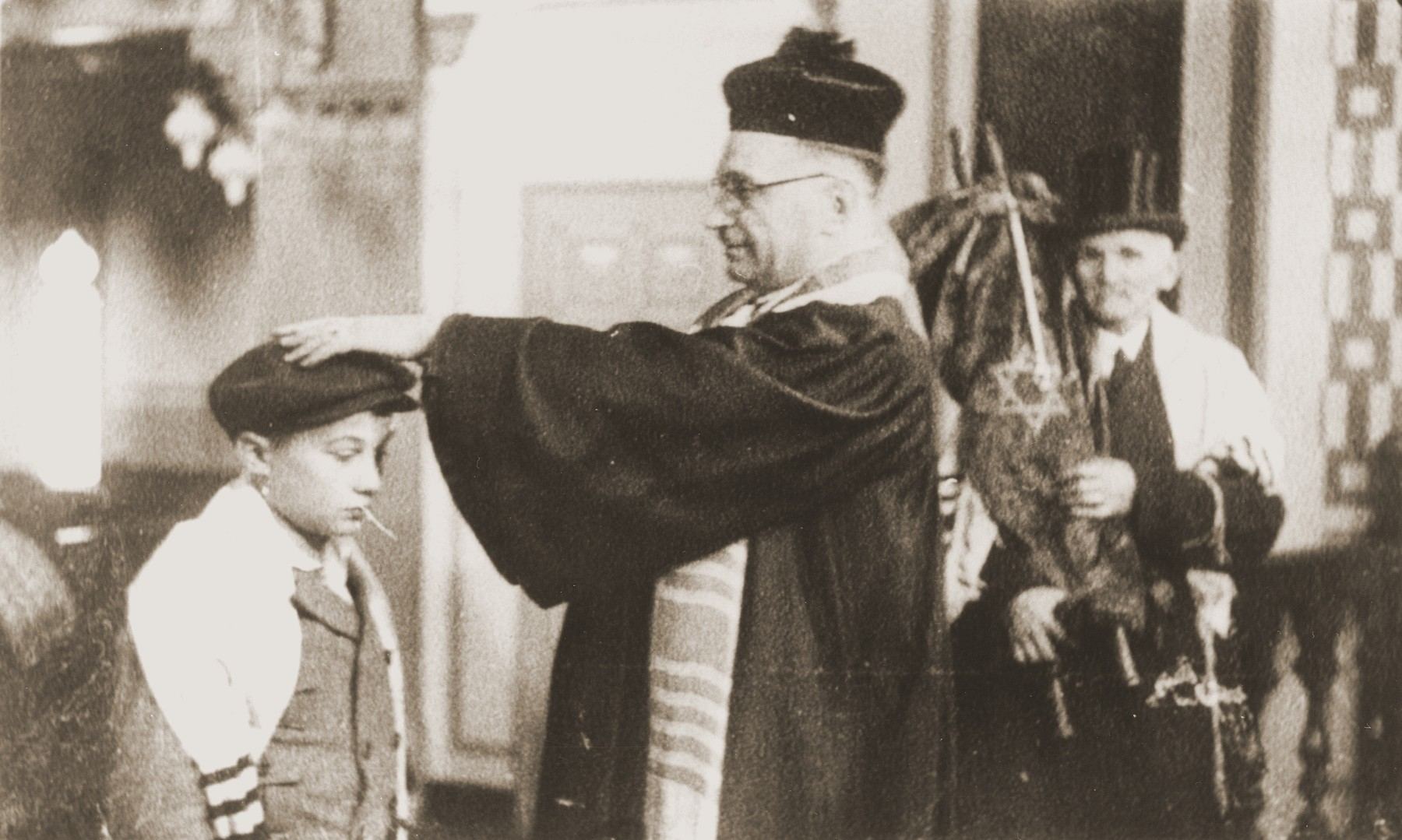At the liberal Zerrennerstrasse synagogue in Pforzheim, Cantor Hermann Levy blesses Siegbert Levy during his bar mitzvah, while Siegbert's great-uncle (holding the Torah scroll) looks on.