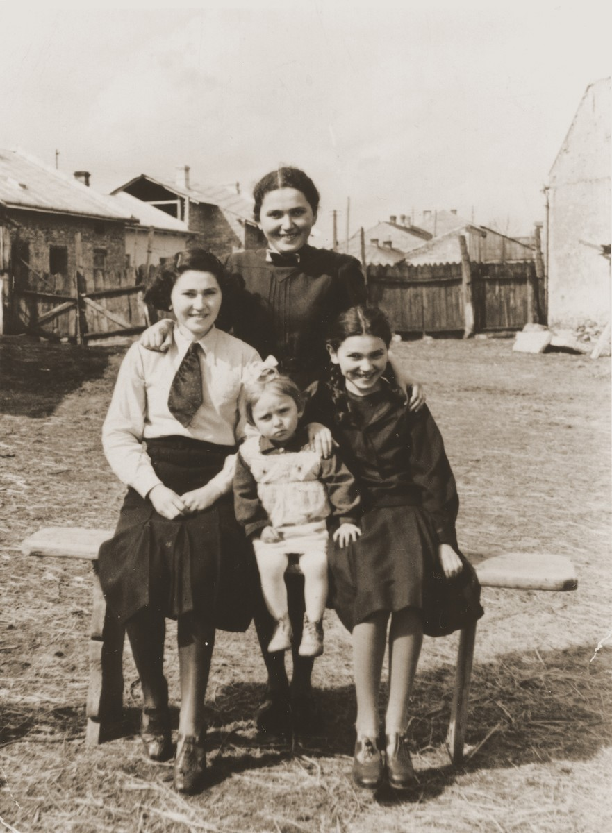 """Members of the extended Braun family pose on a bench in a yard in Brody.  Pictured are the three Braun sisters, Jetka (top), Andzia (right) and Mania (left) with their little cousin Tina.  The Polish inscription on the back of the photo reads, """"[To] my dear relatives/As a souvenir/From Jetka, Mania, Andzia and Tincia."""""""