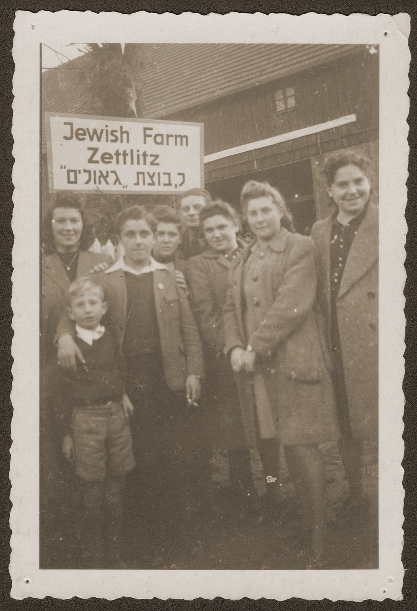 Members of the newly established hachshara [Zionist agricultural collective], Kibbutz Zettlitz, pose in front of the sign at the entrance to the farm.  Abram Gelbart is pictured in front, second from the left.